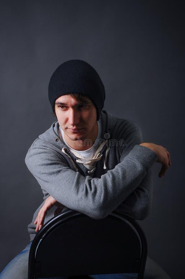 Porträt eines attraktiven jungen männlichen Modells im schwarzen Hut, in den Jeans und im grauen Sweatshirt, Studio, dunkelgrauer stockbild