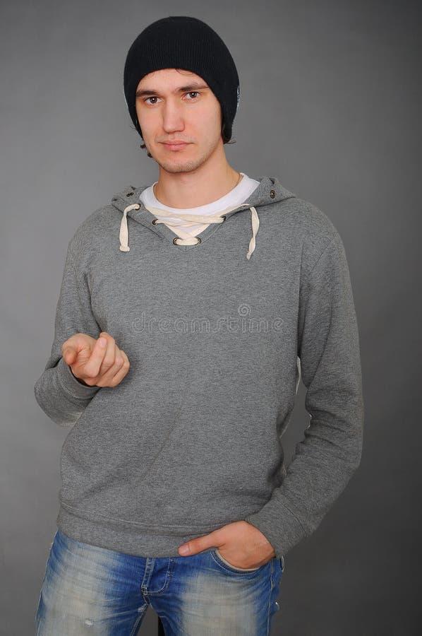 Porträt eines attraktiven jungen männlichen Modells im schwarzen Hut, in den Jeans und im grauen Sweatshirt, Studio, dunkelgrauer lizenzfreies stockbild