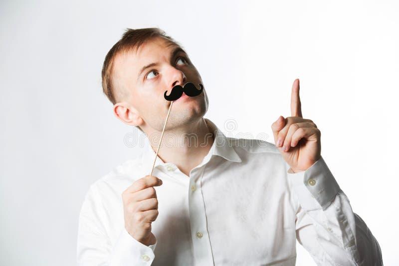 Porträt eines attraktiven jungen Mannes, der einen Retrostilfälschungsschnurrbart trägt stockfotos