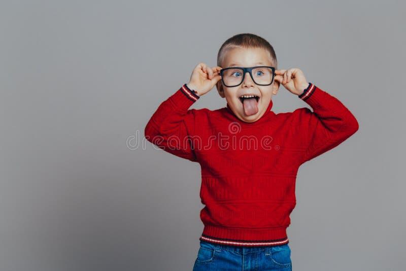 Porträt eines attraktiven lächelnden Jungen in einer roten Strickjacke und in schwarzen Gläsern stockfotografie