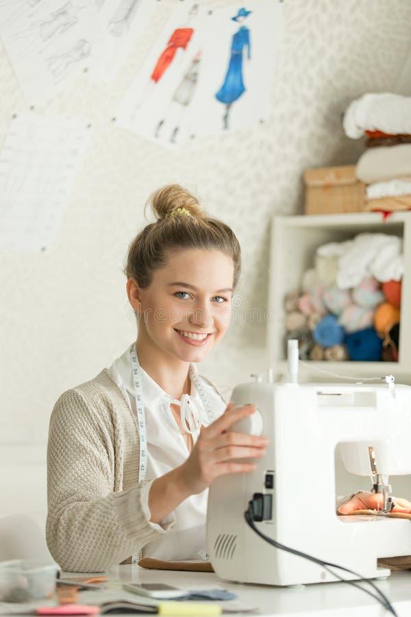 Porträt eines attraktiven Mädchens an Nähmaschine lizenzfreie stockbilder