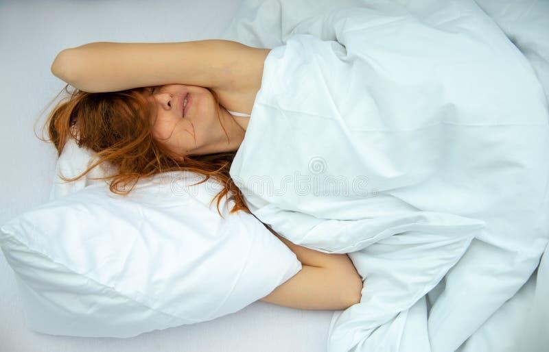Porträt eines attraktiven, zufriedenen, jungen, rothaarigen Frauenlügens entspannte sich im Bett, im Genießen und im Anschmiegen stockfoto