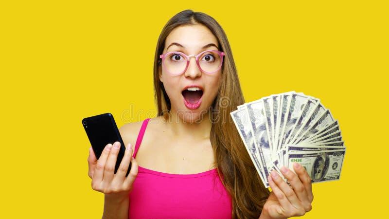 Porträt eines aufgeregten Vertretungsbündels der jungen Frau der Geldbanknoten und des halten Handys über gelbem Hintergrund lizenzfreie stockfotos