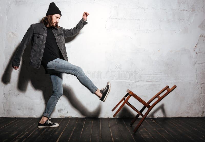 Porträt eines bärtigen Hippie-Mannes, der Stuhl mit Fuß tritt stockfotos