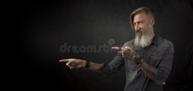 Porträt eines bärtigen Hippies, der mit seinen Fingern auf etwas zeigt, lokalisierte auf einem schwarzen Hintergrund stockfotos