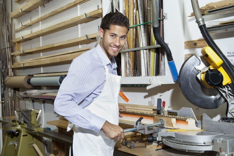 Porträt eines bereitstehenden Rundschreibens des glücklichen jungen Handwerkers sah Maschinerie lizenzfreie stockfotografie