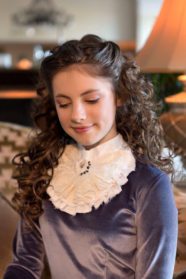 Porträt eines bescheidenen Mädchens in einem hohen Alters- Innen- und der Weinlese altmodischen Kleid der zwanziger Jahre lizenzfreie stockfotos