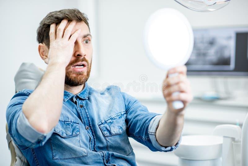 Porträt eines besorgten Mannes im zahnmedizinischen Büro lizenzfreie stockfotos
