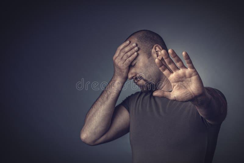 Porträt eines betonten Mannes mit seinen Augen geschlossen und seiner Hand auf seiner Stirn lizenzfreies stockfoto