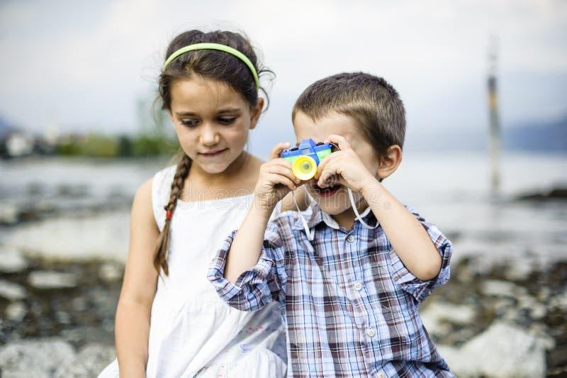 Porträt eines Bruders und der Schwesterkinder mit Spielzeugkamera lizenzfreies stockfoto
