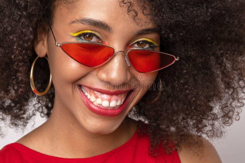 Porträt eines dunkelhäutigen Mädchens in den roten Gläsern stockfotos
