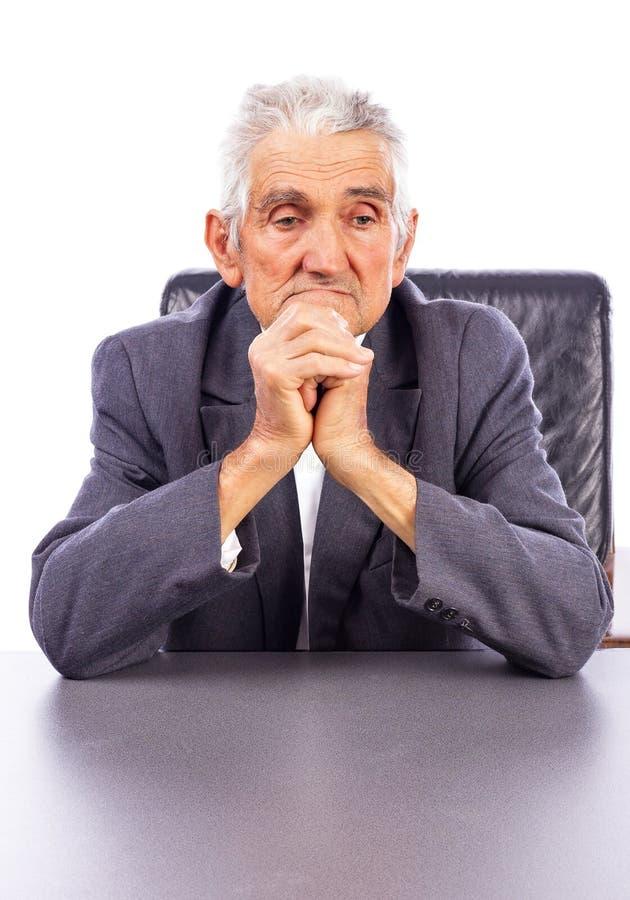 Porträt eines durchdachten älteren Mannes, der seine Hände zusammenhält lizenzfreies stockfoto