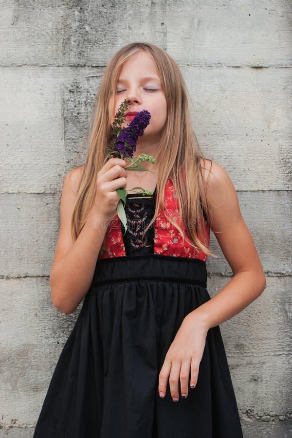 Porträt eines durchdachten Mädchens, eine Blume halten lizenzfreies stockfoto