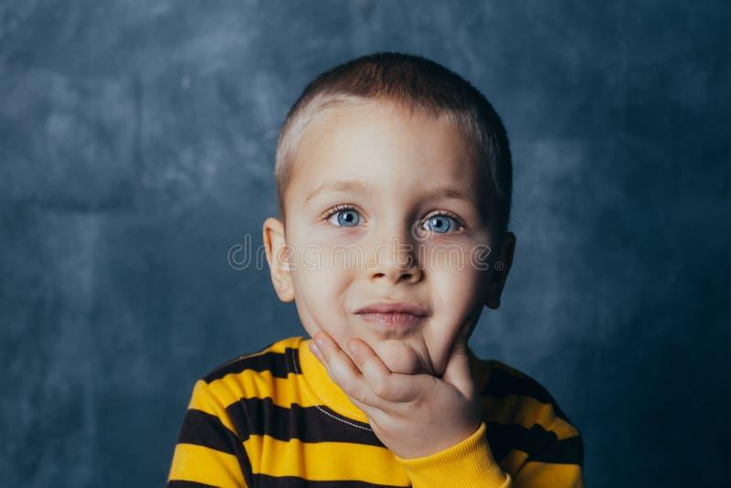 Porträt eines durchdachten netten kleinen Kindes mit der Hand, die Gesicht, Kamera betrachtend berührt stockfoto