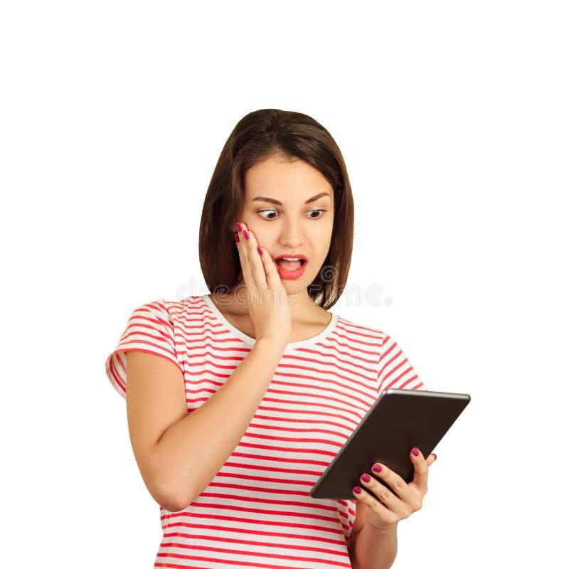 Porträt eines entsetzten jungen Mädchens, das einen Tablet-Computer hält und ihn betrachtet emotionales Mädchen lokalisiert auf w lizenzfreies stockfoto