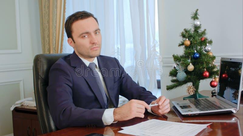 Porträt eines ernsten jungen hübschen Geschäftsmannes, der in camera, ernstes durchdachtes schaut stockbild