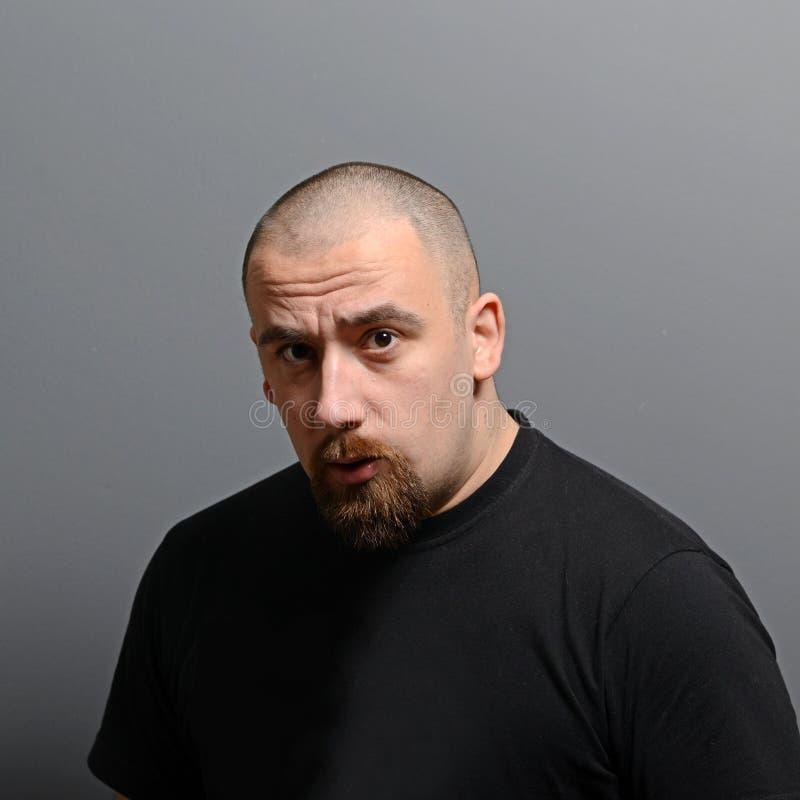 Porträt eines ernsten Mannes gegen grauen Hintergrund stockbilder