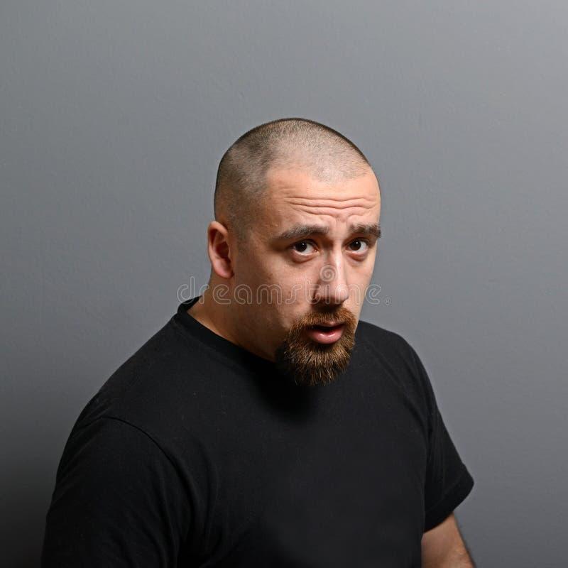 Porträt eines ernsten Mannes gegen grauen Hintergrund stockfotos