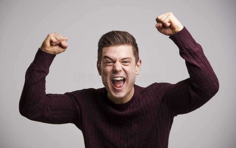 Porträt eines feiernden jungen weißen Mannes mit den Armen oben lizenzfreie stockfotos