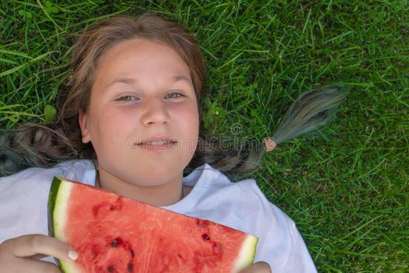 Porträt eines fetten Mädchens von 13 Jahren alt, wer auf dem Gras mit einer Wassermelone in ihren Händen liegt lizenzfreie stockfotos