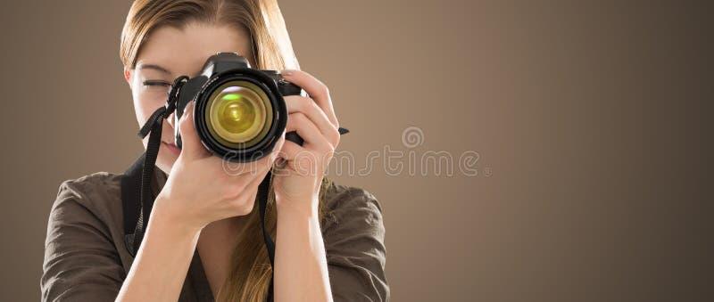 Porträt eines Fotografen, der ihr Gesicht mit Kamera bedeckt lizenzfreie stockbilder