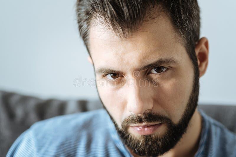 Porträt eines freudlosen gutaussehenden Mannes, der Sie betrachtet lizenzfreie stockfotografie