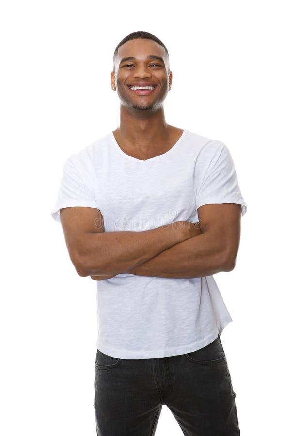 Porträt eines freundlichen jungen Mannes, der mit den Armen gekreuzt lächelt stockbild