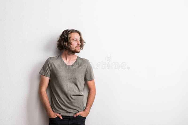 Porträt eines frohen jungen Mannes mit dem langen gewellten Haar in einem Studio, Hände in den Taschen stockfoto