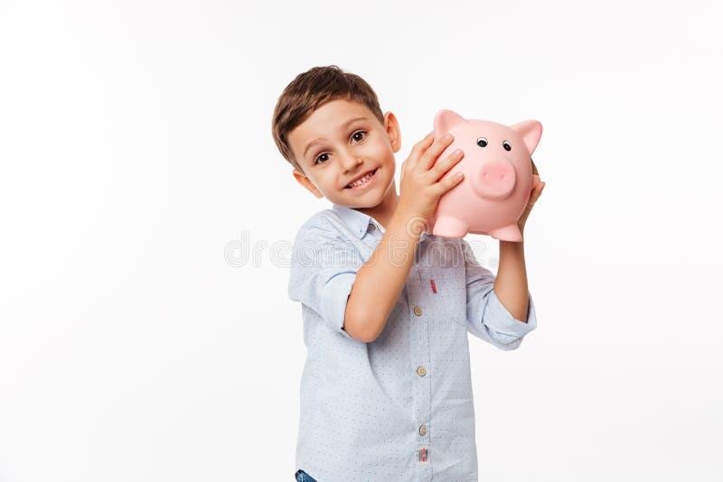 Porträt eines frohen netten Kleinkindes, das Sparschwein hält stockfotografie