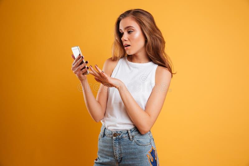 Porträt eines frustrierten verwirrten Mädchens, das Handy betrachtet lizenzfreies stockfoto