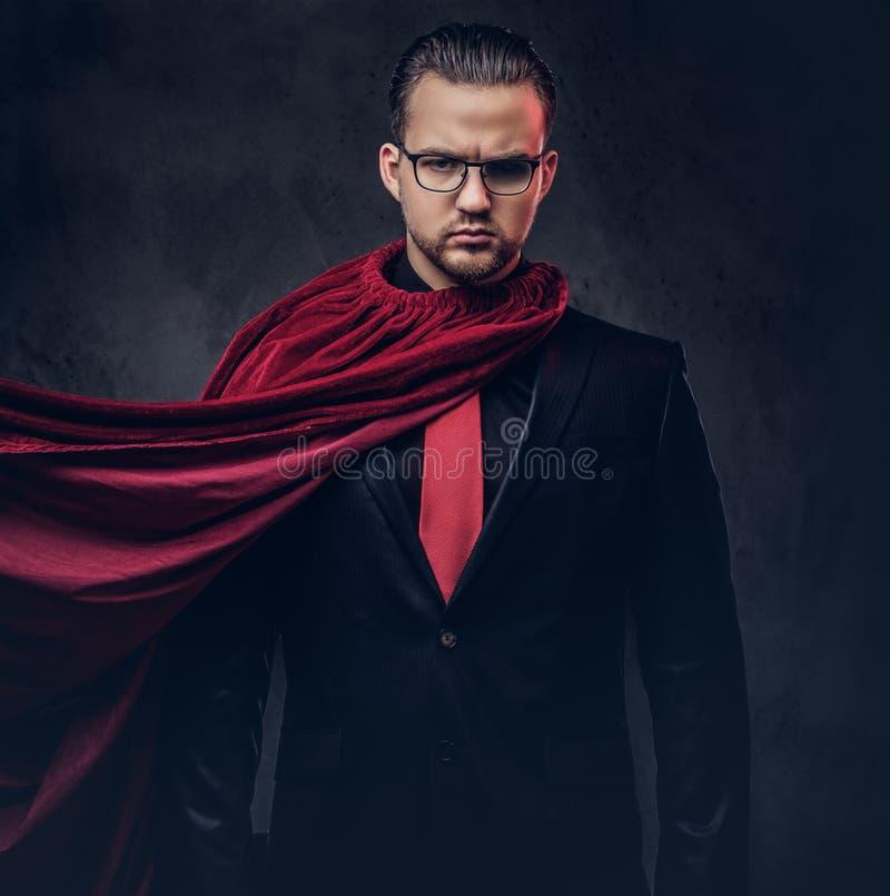 Porträt eines Geniesuperhelden in einem schwarzen Anzug mit einer roten Bindung auf einem dunklen Hintergrund lizenzfreies stockbild