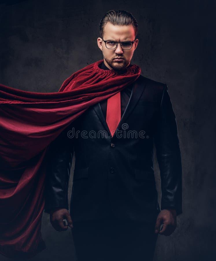Porträt eines Geniesuperhelden in einem schwarzen Anzug mit einer roten Bindung auf einem dunklen Hintergrund lizenzfreie stockbilder