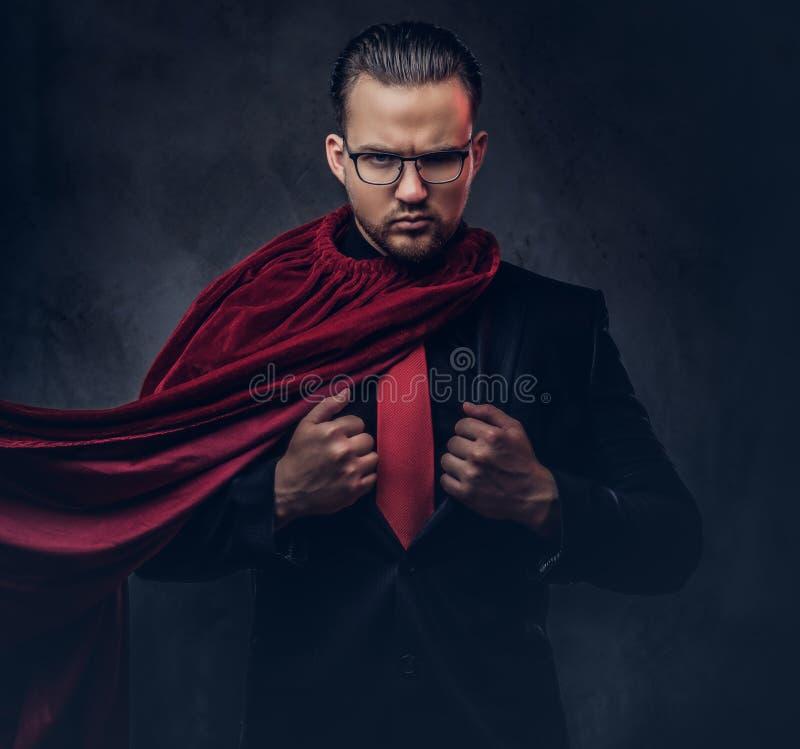 Porträt eines Geniesuperhelden in einem schwarzen Anzug mit einer roten Bindung auf einem dunklen Hintergrund stockbilder