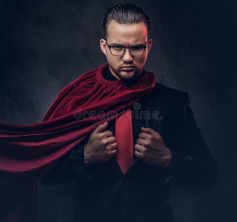 Porträt eines Geniesuperhelden in einem schwarzen Anzug mit einer roten Bindung auf einem dunklen Hintergrund lizenzfreie stockfotografie