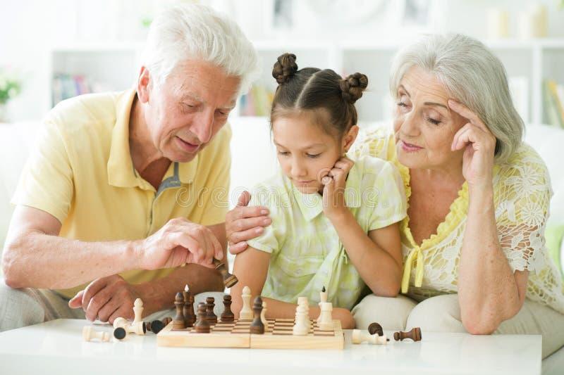 Porträt eines glücklichen älteren Paares spielen Schach stockbild