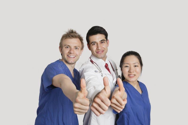 Porträt eines glücklichen Ärzteteams, das Daumen oben über grauem Hintergrund gestikuliert lizenzfreie stockfotos