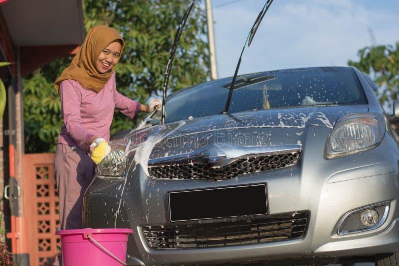 Porträt eines glücklichen asiatischen hijab Frauen-Reinigungsautos vor ihrer Garage stockfotos