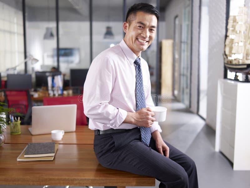Porträt eines glücklichen asiatischen Unternehmensleiters im Büro stockfotos
