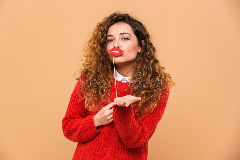 Porträt eines glücklichen hübschen Mädchens, das gefälschte Lippen hält lizenzfreie stockfotografie