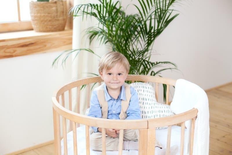 Porträt eines glücklichen Jungen, der in einem Babyfeldbett spielt Der Junge sitzt allein in einer Krippe in der Kindertagesstätt lizenzfreie stockfotos