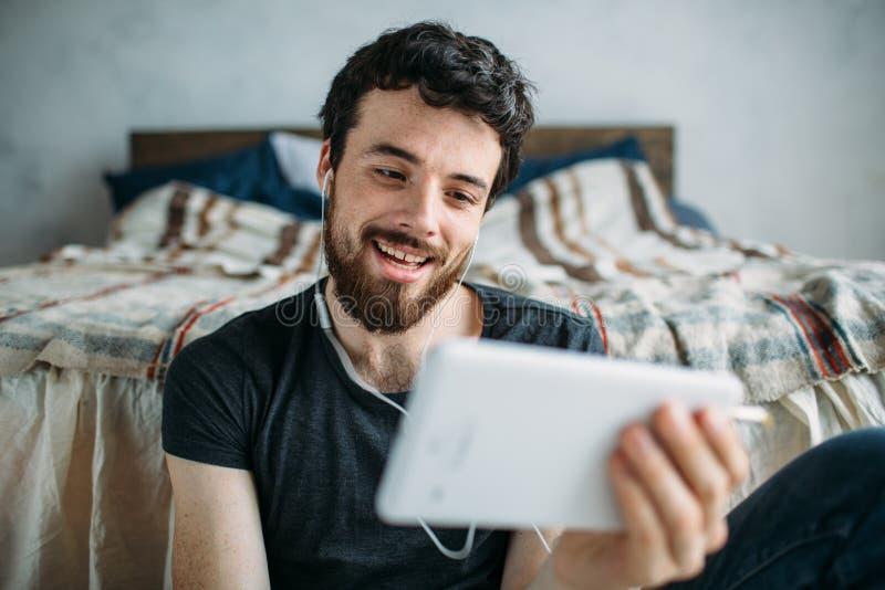 Porträt eines glücklichen jungen Mannes, der eine Fernsehshow auf einem Tablet-Computer sich entspannt und aufpasst stockbilder