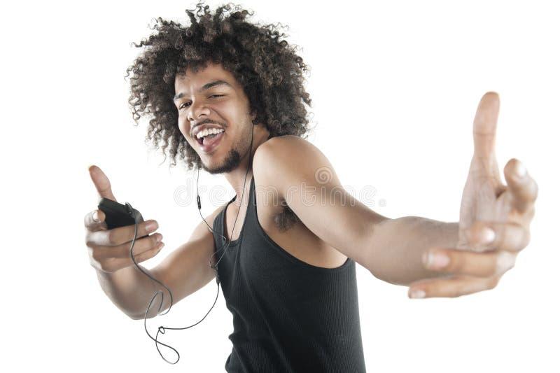 Porträt eines glücklichen jungen Mannes im Westentanzen zu den Melodien des MP3-Players über weißem Hintergrund stockfotografie