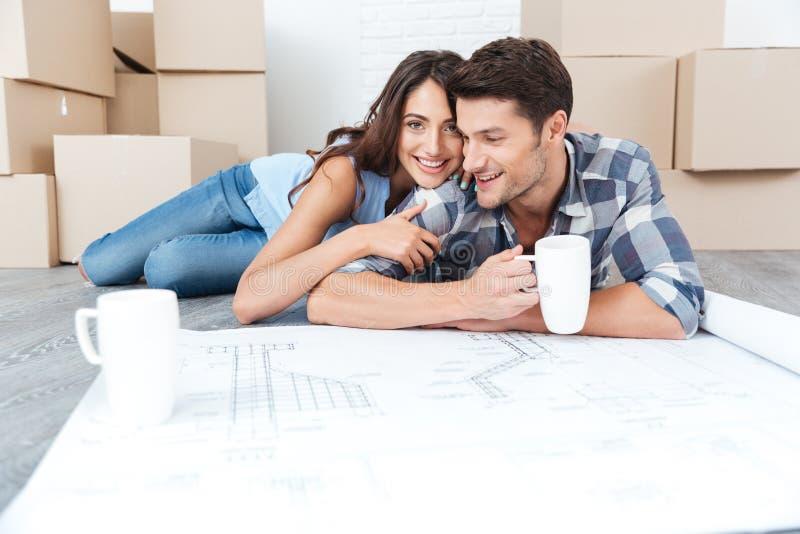 Porträt eines glücklichen jungen Paares, das die Pläne betrachtet stockfotos