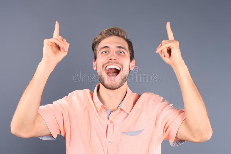 Porträt eines glücklichen jungen zufälligen Mannes, der oben auf den Kopienraum lokalisiert über grauem Hintergrund zeigt stockbilder