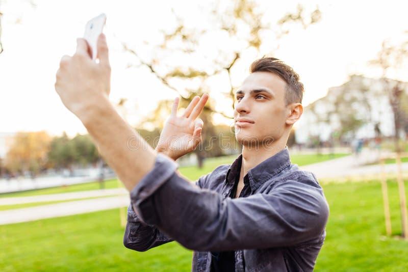 Porträt eines glücklichen Kerls, in der Sonnenbrille, stehend im Parkesprit stockfotografie