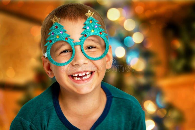 Porträt eines glücklichen Kindes auf einem Weihnachtsbaumhintergrund Lächelnder Junge mit Gläsern lizenzfreies stockfoto