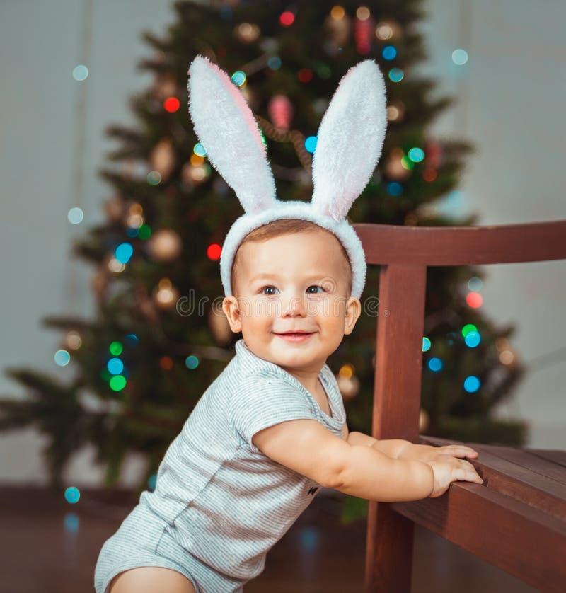 Porträt eines glücklichen Kindes nahe einem Weihnachtsbaum stockbild
