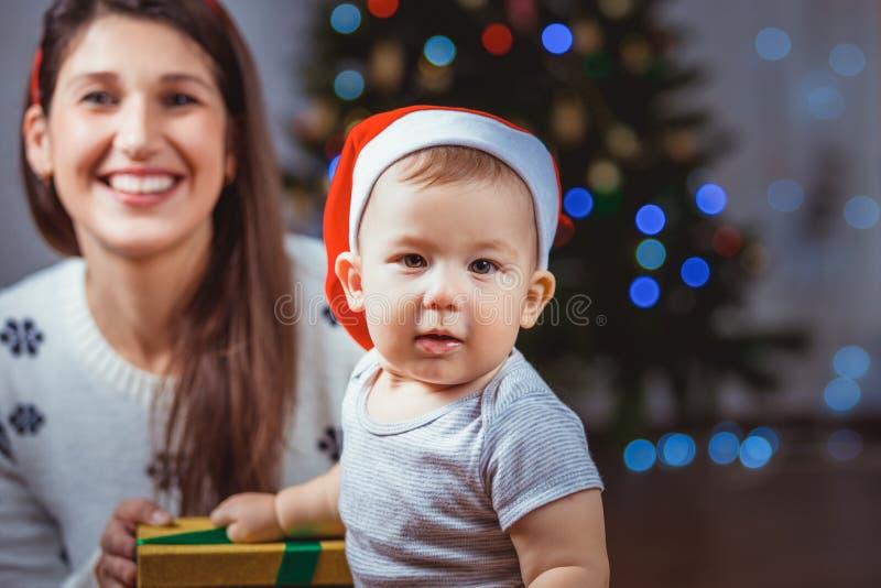 Porträt eines glücklichen Kindes und der Frau nahe einem Weihnachtsbaum stockbild