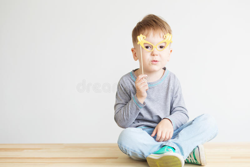 Porträt eines glücklichen Kleinkindes mit gelben Papiergläsern lizenzfreie stockfotografie