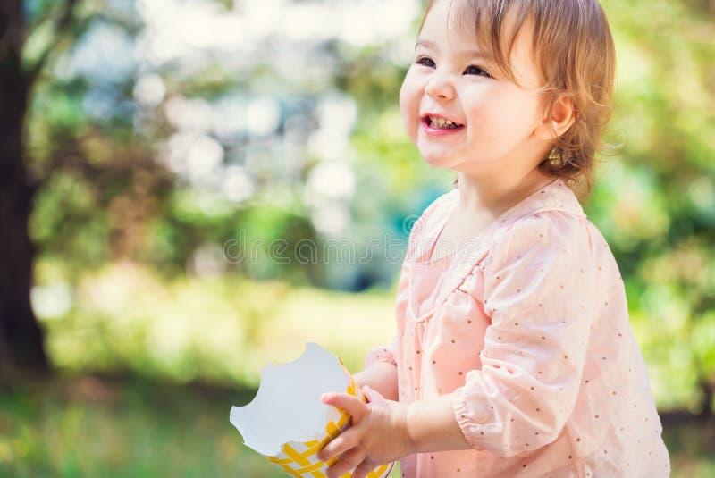 Porträt eines glücklichen Kleinkindmädchens, das mit einem großen Lächeln spielt stockfotos